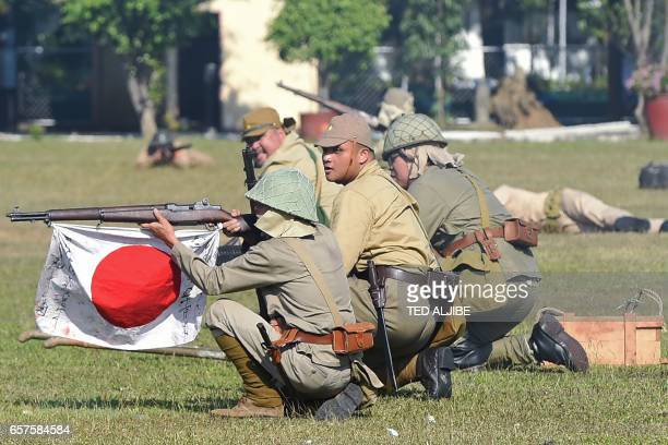 Members of the Living History Society acting as Japanese soldiers reenact a scene of the Battle of the Pockets between allied and Japanese forces...