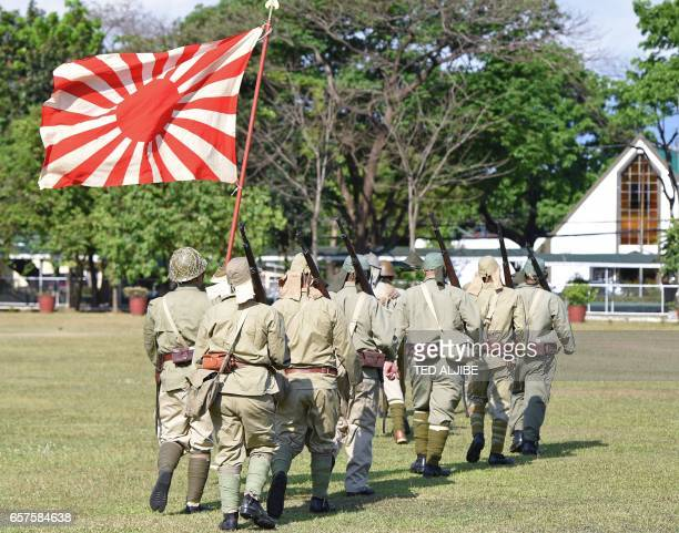 Members of the Living History Society acting as Japanese soldiers march after reenacting a scene of the Battle of the Pockets between allied and...