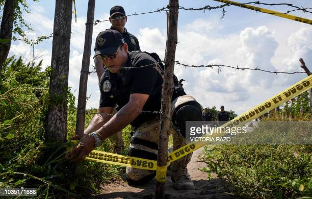 Members of the local attorney's opffice cordon off on September 17 the site where a mass grave was found in El Arbolillo, Alvarado municipality, in...