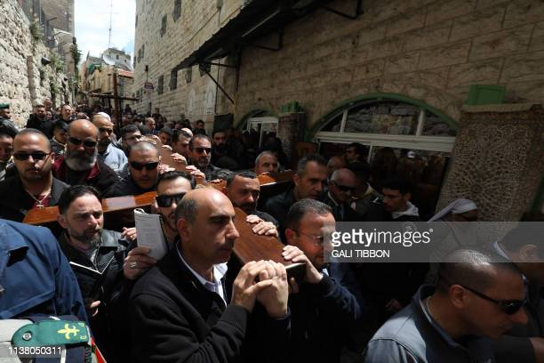 Members of the local Catholic Palestinian parish carry a wooden cross along the Via Dolorosa in Jerusalem's Old City during the Good Friday...