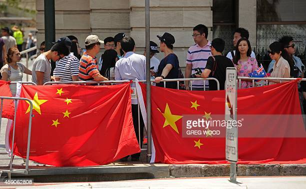 Members of the local Chinese community wait to try and catch a glimpse of China's President Xi Jinping as he drives by during the G20 Summit in the...