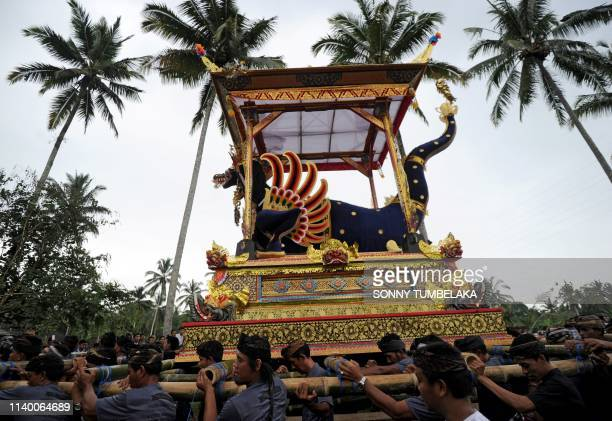 Members of the local community carry a sarcophagus for the cremation of two late family members of Indonesian national hero I Gusti Ngurah Rai in the...