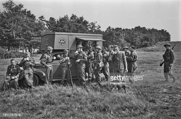 Members of the Local Defence Volunteers , or Home Guard, enjoy cups of tea and refreshments at a YMCA tea car mobile canteen after taking part in a...
