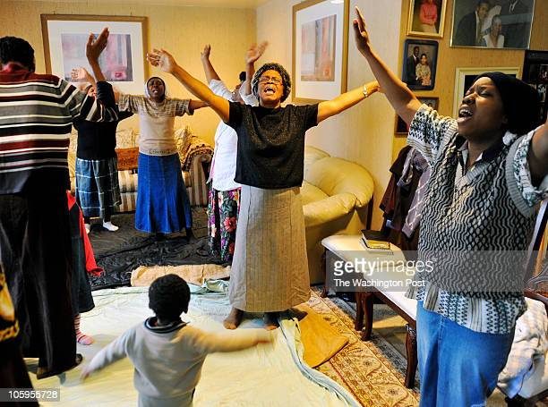 Members of the local Haitian community pray for loved ones in their pastor's Silver Spring living room in the wake of yesterday's major earthquake LR...