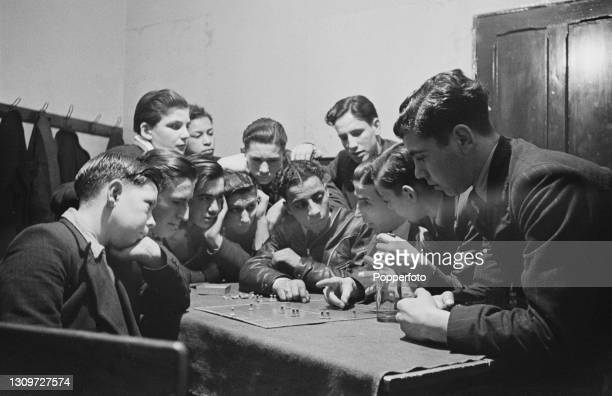 Members of the London Square Boys Club football team crowd round to receive a lesson in tactics from club leader Mr Turner at the club's home in...