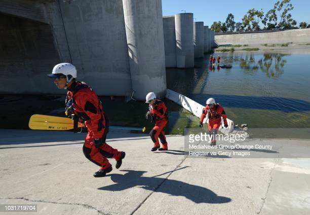 Members of the Long Beach Swift Water Rescue Team exit the Los Angeles River south of Willow St on Wednesday ///ADDITIONAL INFORMATION Slug...