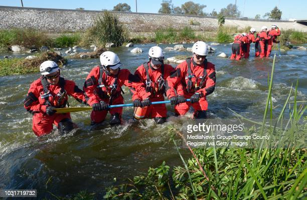 Members of the Long Beach Swift Water Rescue Team practice shallow water crossings in the Los Angeles River south of Willow St on Wednesday...