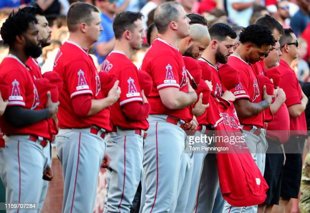 Members of the Los Angeles Angels hold the jersey of Tyler Skaggs of the Los Angeles Angels during a moment of silence before taking on the Texas...