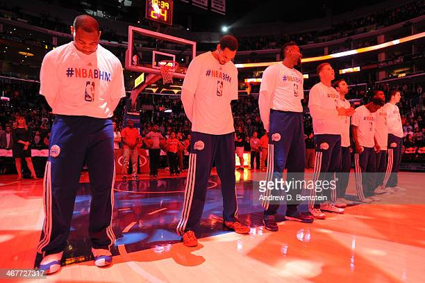 Members of the Los Angeles Clippers stand in observance of the national anthem before a game against the Toronto Raptors at STAPLES Center on...