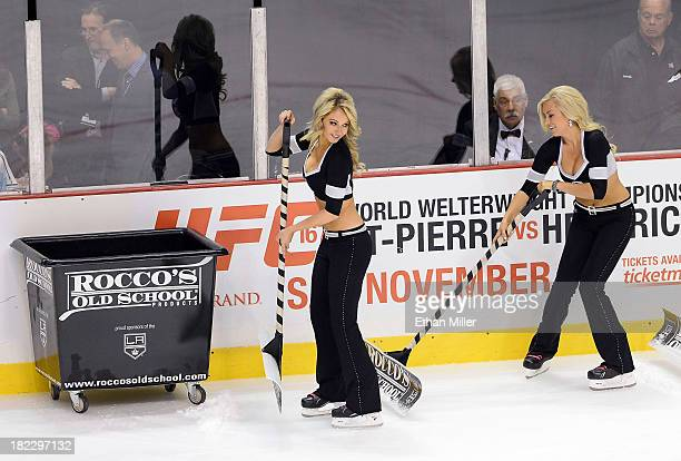 Members of the Los Angeles Kings ice girls Ashley Covert and Allison Ally Mello clean the ice during the team's preseason game against the Colorado...