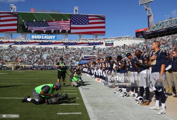 Members of the Los Angeles Rams stand during the national anthem on the field prior to the start of their game against the Jacksonville Jaguars at...