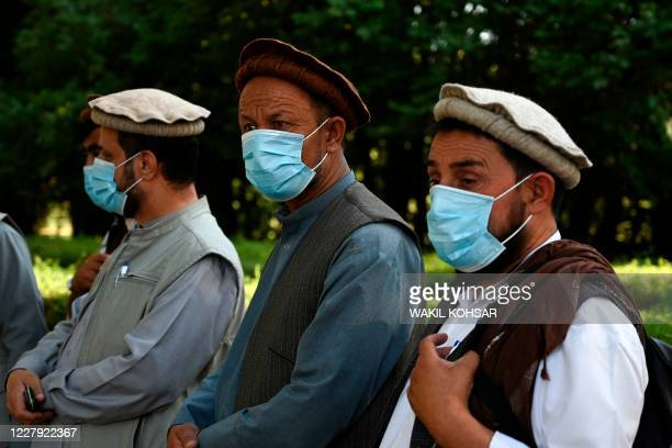 Members of the Loya jirga wearing facemasks wait to be tested for the COVID-19 coronavirus at the Kabul Polytechnic University, in Kabul on August 5,...