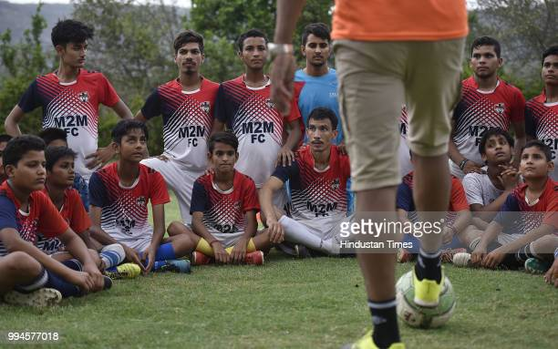 Members of the M2M football club listen to their coach during a practice session in a park at Ghamroj Village on June 27 2018 near Gurugram India...