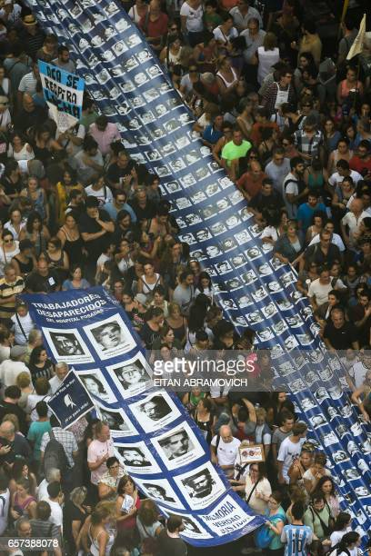 Members of the Madres de Plaza de Mayo and Abuelas de Plaza de Mayo human rights organizations are joined by thousands of demonstratorsas they carry...