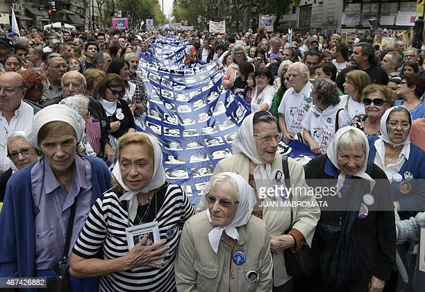 Members of the Madres de Plaza de Mayo Human Rights organization and demonstrators carry a large banner with portraits of people disappeared in the...