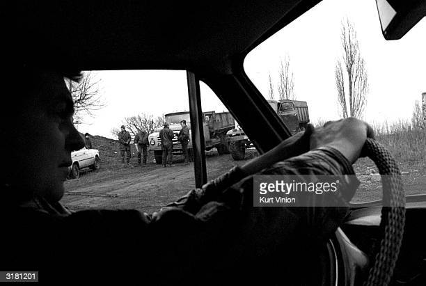 Members of the mafia wait for coal to be loaded on their trucks February 25 2002 near Snezhnoye Ukraine In order for miners to work they must pay...