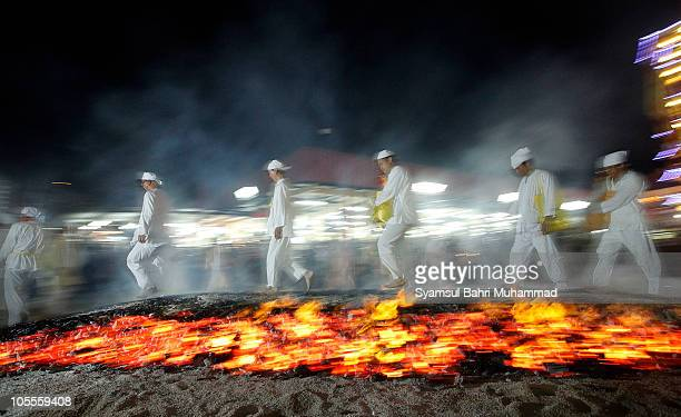 Members of the Malaysian ethnic Chinese community walk barefoot on burning coals as they perform firewalking on the last day of the Nine Emperor Gods...