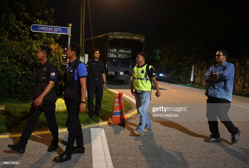 Members of the Malaysian police enter into the road leading to the former Prime Minister Najib Razak's residence in Kuala Lumpur on May 16, 2018. - Malaysia's toppled leader Najib Razak was on may 14 accused by a former top graft fighter of blocking probes into a massive financial scandal, as the country's new prime minister got down to work after a historic poll win.