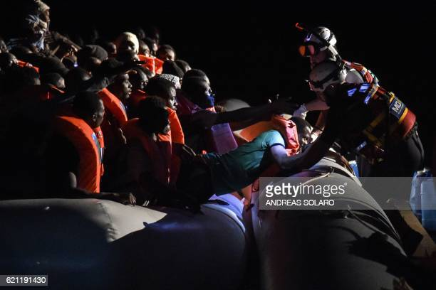 Members of the Maltese NGO MOAS helps a man to board a small rescue boat during a rescue operation of 146 migrants and refugees by the Topaz...