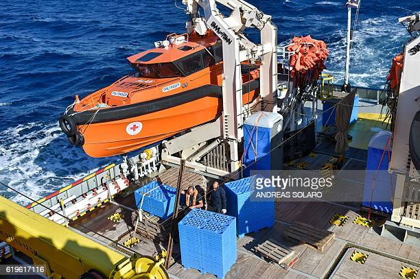 Members of the Maltese NGO MOAS work on the desck of the Topaz Responder ship during a navigation to reach the rescue area off the Lybian coasts in...