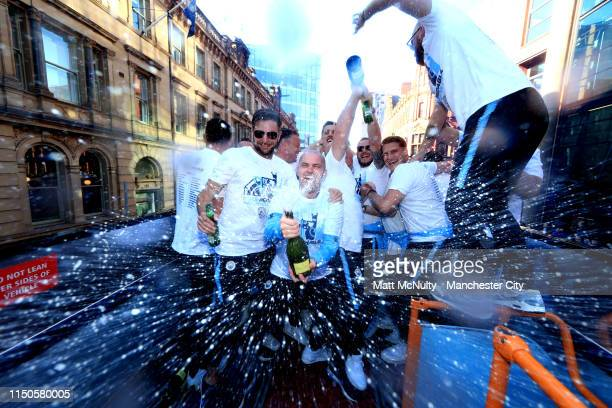 Members of the Manchester City backroom staff celebrate on the team bus during the Manchester City Teams Celebration Parade on May 20, 2019 in...