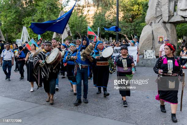 Members of the Mapuche community walk as they play a musical instrument called kultrung while performing a ceremony at Plaza de Armas during a...
