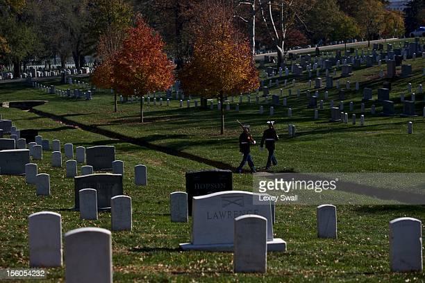 Members of the Marine Corps Honor Guard make their way across Arlington National Cemetery on Veteran's Day November 11 2012 in Arlington Virginia...