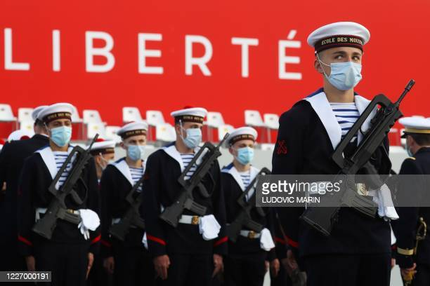 TOPSHOT Members of the Marine Nationale officer from the Ecole des Mousses wearing protective facemasks attends prior to the annual Bastille Day...