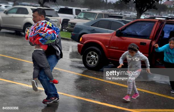 Members of the Martinez family run in strong wind and rain to get inside the Germain Arena to take shelter The extended family had tried to stay in...