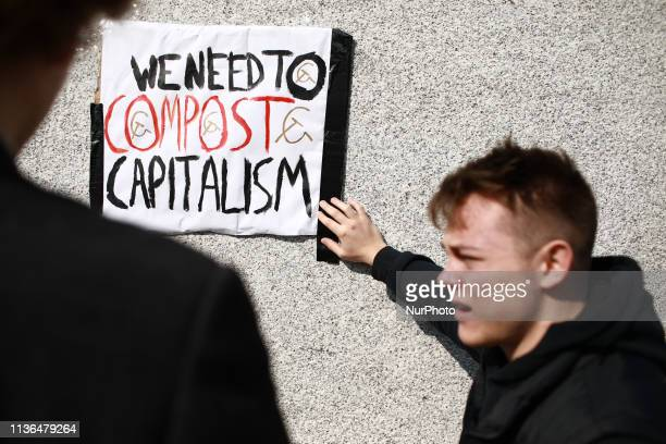 Members of the Marxist Student Federation fix an anticapitalist sign to the base of the statue of Winston Churchill in Parliament Square ahead of the...