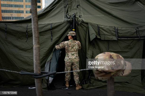 Members of the Maryland Army National Guard work to set up a triage tent in the parking lot outside of the emergency room at Adventist HealthCare...