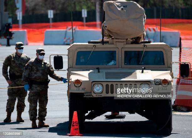 Members of the Maryland National Guard guard a testing site in a parking lot at FedEx Field on March 30, 2020 in Landover, Maryland. - The US has...