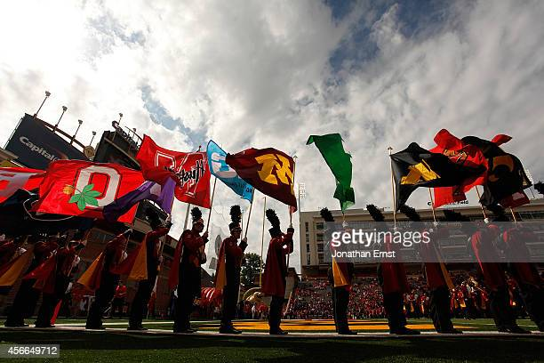 Members of the Maryland Terrapins marching band carry the flags of fellow Big Ten schools before their first home game as members of the conference a...