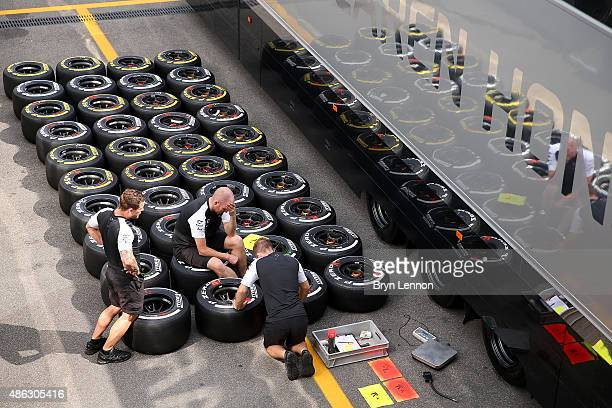 Members of the McLaren team speak in the paddock next to sets of Pirelli tyres during previews to the Formula One Grand Prix of Italy at Autodromo di...