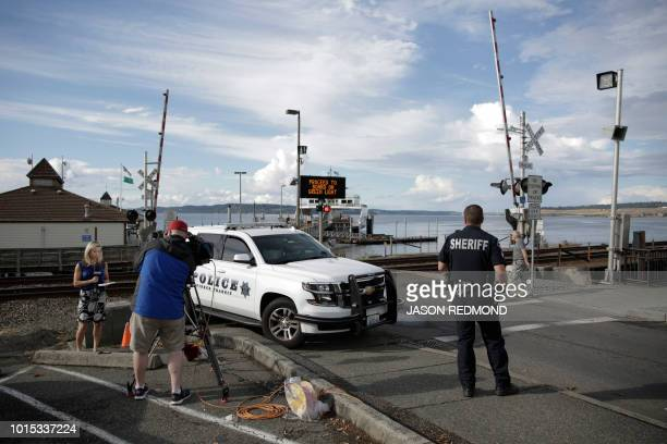 Members of the media and a Pierce County Sheriffs deputy are pictured near the Steilacoom Ferry dock which takes investigators to Ketron Island the...