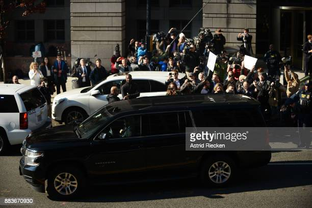Members of the media and demonstrators gather around the car carrying Michael Flynn former national security advisor to President Donald Trump as he...