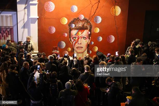 Members of the media and public gather by a mural of David Bowie in Brixton on January 11 2016 in London England British music and fashion icon David...