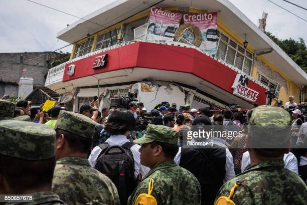 Members of the media and residents gather around Enrique Pena Nieto Mexico's president not pictured during a tour to survey the damage from a 71...