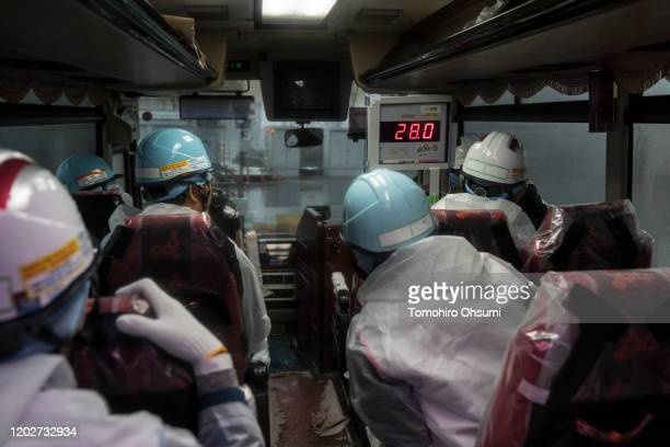 Members of the media and Tokyo Electric Power Co. Employees look at a monitor showing radiation levels inside a tour bus at the Fukushima Dai-ichi...