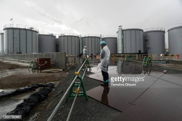 Members of the media and Tokyo Electric Power Co. Employees walk past storage tanks for radioactive water at the Fukushima Dai-ichi nuclear power...