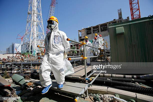Members of the media and Tokyo Electric Power Co employees wearing protective suits and masks walk towards the common spent fuel facility during a...