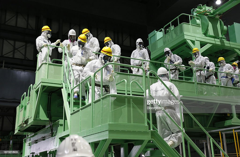 Members of the media and Tokyo Electric Power Co. (Tepco) employees wearing protective suits and masks walk down the steps of a fuel handling machine on the spent fuel pool inside the building housing the No. 4 reactor at the Fukushima Dai-ichi nuclear power plant in Okuma, Fukushima Prefecture, Japan, on Thursday, Nov. 7, 2013. Tepco, which returned to profitability in its first-half earnings report on Oct. 31, is handling an estimated 11 trillion yen ($112 billion) cleanup of the nuclear plant wrecked by an earthquake and tsunami in 2011. Photographer: Kimimasa Mayama/Pool via Bloomberg