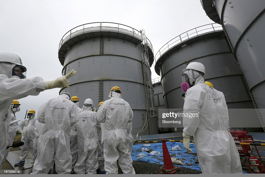 Members of the media and Tokyo Electric Power Co. (Tepco) employees wearing protective suits and masks stand in front of storage tanks for radioactive water at the Fukushima Dai-ichi nuclear power plant in Okuma, Fukushima Prefecture, Japan, on Thursday, Nov. 7, 2013. Tepco, which returned to profitability in its first-half earnings report on Oct. 31, is handling an estimated 11 trillion yen ($112 billion) cleanup of the nuclear plant wrecked by an earthquake and tsunami in 2011. Photographer: Kimimasa Mayama/Pool via Bloomberg