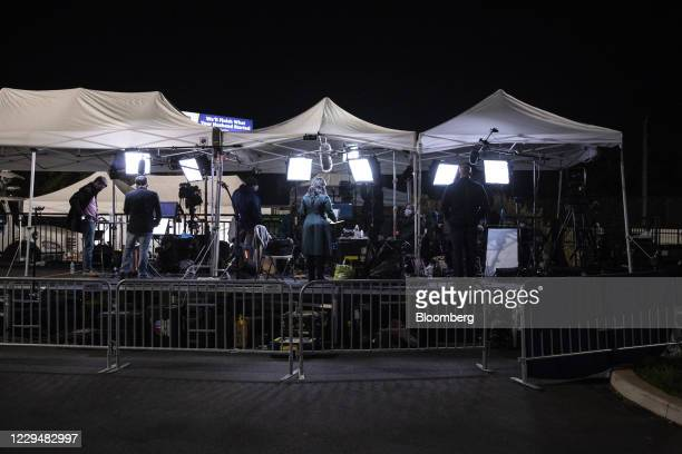 Members of the media appear on television from the campaign headquarters event site parking lot of Joe Biden, 2020 Democratic presidential nominee,...