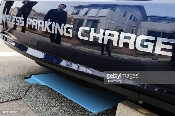 Members of the media are reflected in a Toyota Motor Corp Prius PHV plugin hybrid vehicle as it parks above the company's wireless vehicle charging...