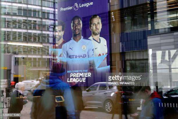 Members of the media are reflected in the glass at the headquarters of the English Premier League in London on March 13 2020 The English Premier...