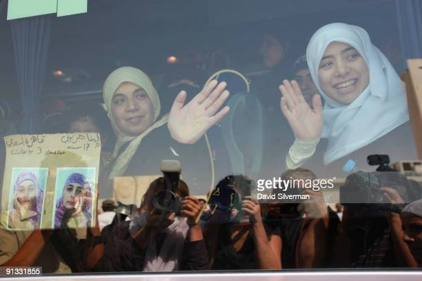 Members of the media are reflected in the windows of a bus bringing waving freed Palestinian women prisoners to meet Palestinian President Mahmoud...