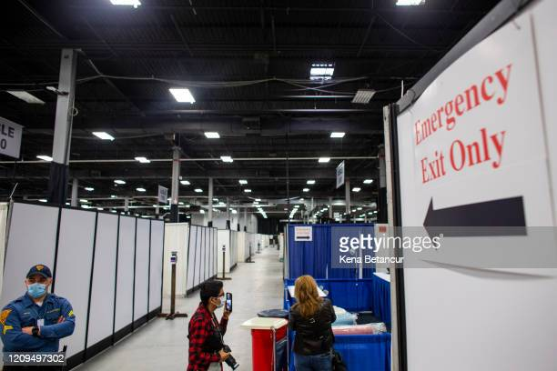 Members of the media attend a tour inside the New Jersey Convention Center on April 8, 2020 in Edison, New Jersey. Workers set up a field medical...