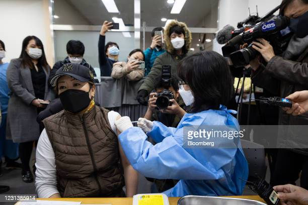 Members of the media document a nurse administering a dose of the AstraZeneca Plc Covid-19 vaccine at a public health center in Incheon, South Korea,...