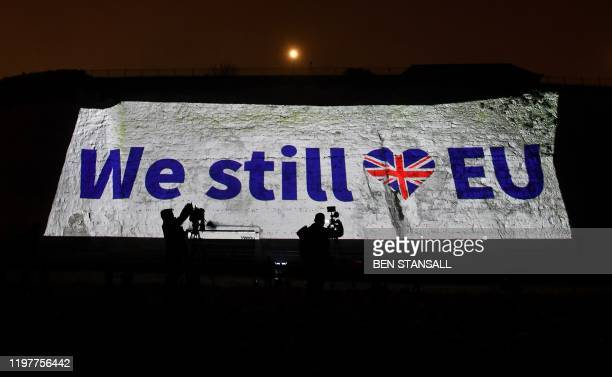 Members of the media film a proEU message projected onto the cliffs in Ramsgate southern England on January 31 2020 as Britain prepares to leave the...